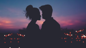 Couple in front of a city at sunset
