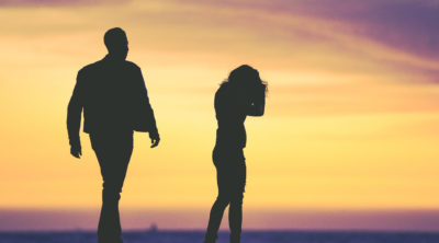 silhouette of couple arguing at sunset