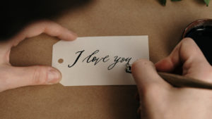 Person writing I love you on a label card