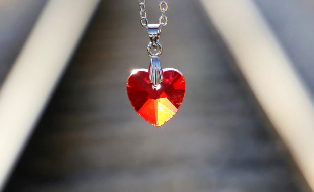 orange and red jewel necklace in the shape of a heart hanging in the center of the image