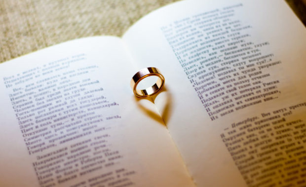 picture of an open book of poems with a gold engagement ring sitting in the center