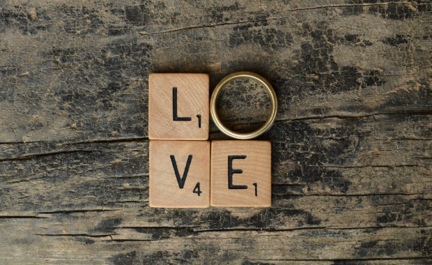 Block letters that spell out love on a table with a wedding ring to represent the 'O'