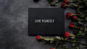 a black sign on a grey table that reads love yourself with red roses around it