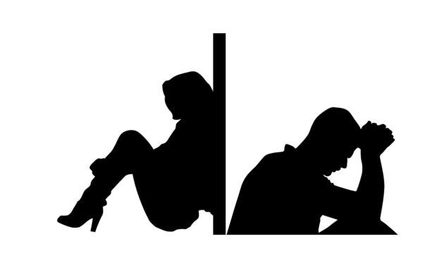 silhouette of couple sitting on opposite sides of a closed door sad