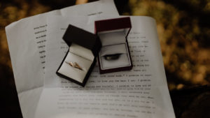 two boxes with wedding bands, one gold and the other brown, sitting onto of wedding vow papers
