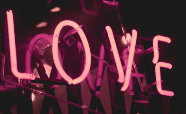 "a light up pink ""LOVE"" sign in the dark"