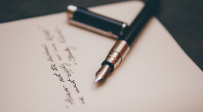 a black pen laying on cursive written words of poetry on a paper