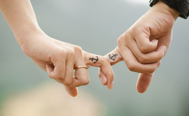 two people with their pointer fingers interlocked. Both have a anchor tattoo on their finger