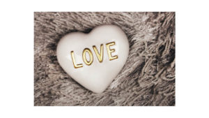 a white heart with golden letters that spell out love sitting on a furry grey background