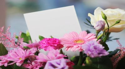 flower arrangements of pink, purple, white, and yellow flowers with a card in the middle of them