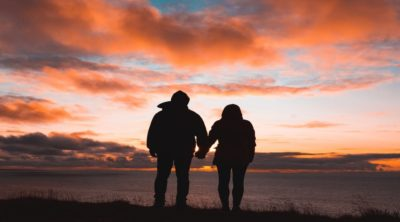 silhouette of couple holding hands and watching the sunset with orange clouds in the sky