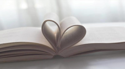 open book with pages folded into a heart in the middle
