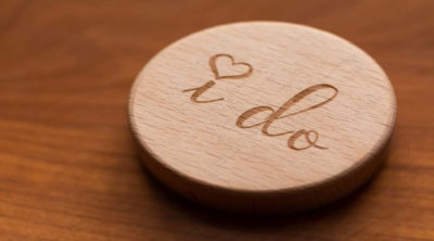 "a wooden circle that reads ""I do"" with a heart dotting the eyes on a table"