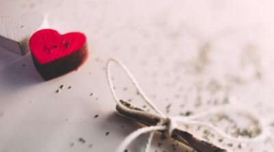 red and white heart laying on white table with sparkles around them and a stick with a box tied on it