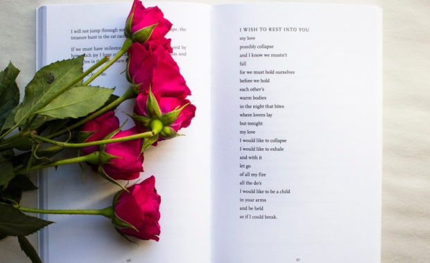 open poetry book on white background with red poems sitting on a page where a love poem is written